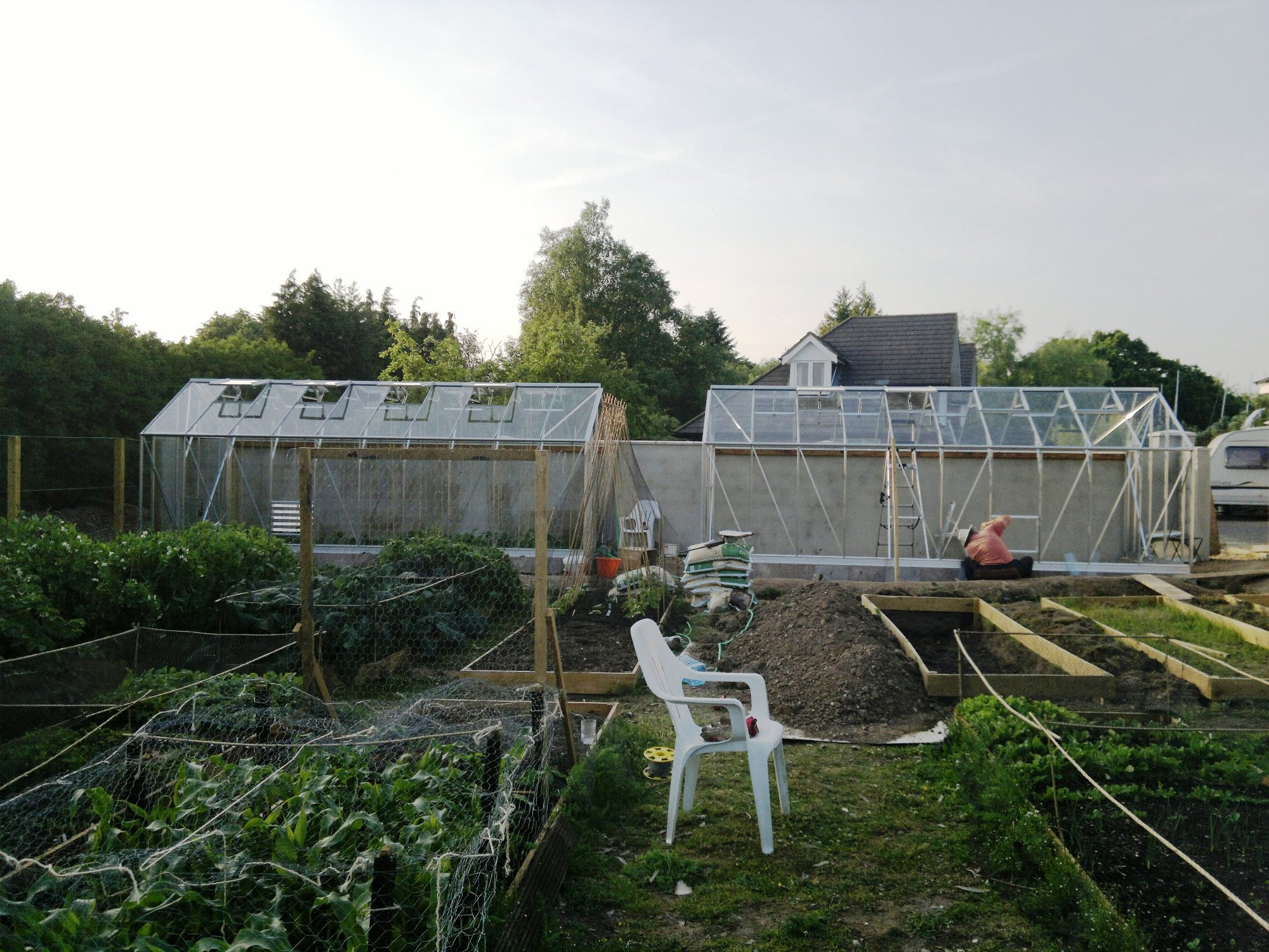 Second glasshouse being bolted down to the dwarf walls