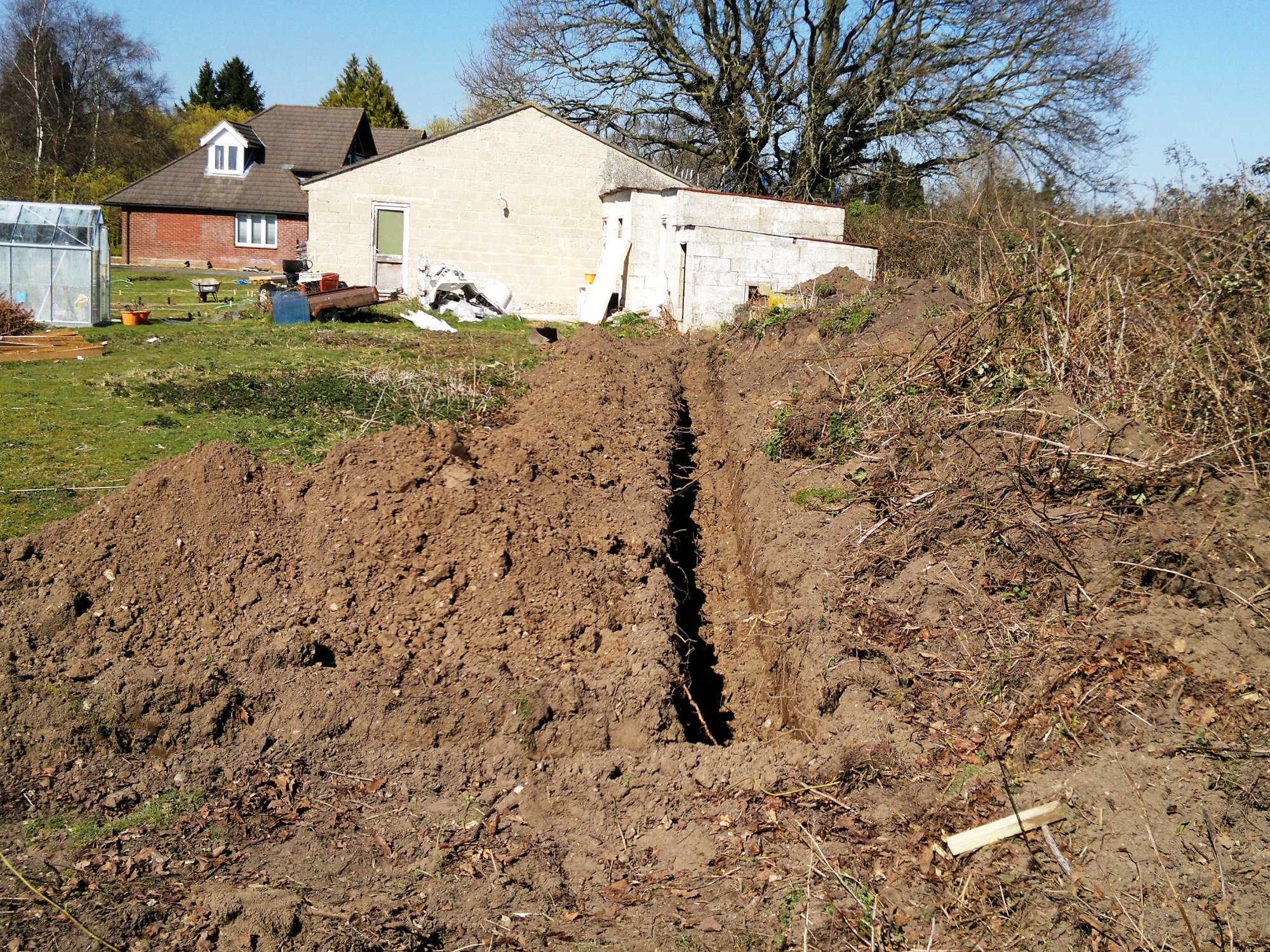 Trench returning to end wall of outbuildings to form the eastern boundary