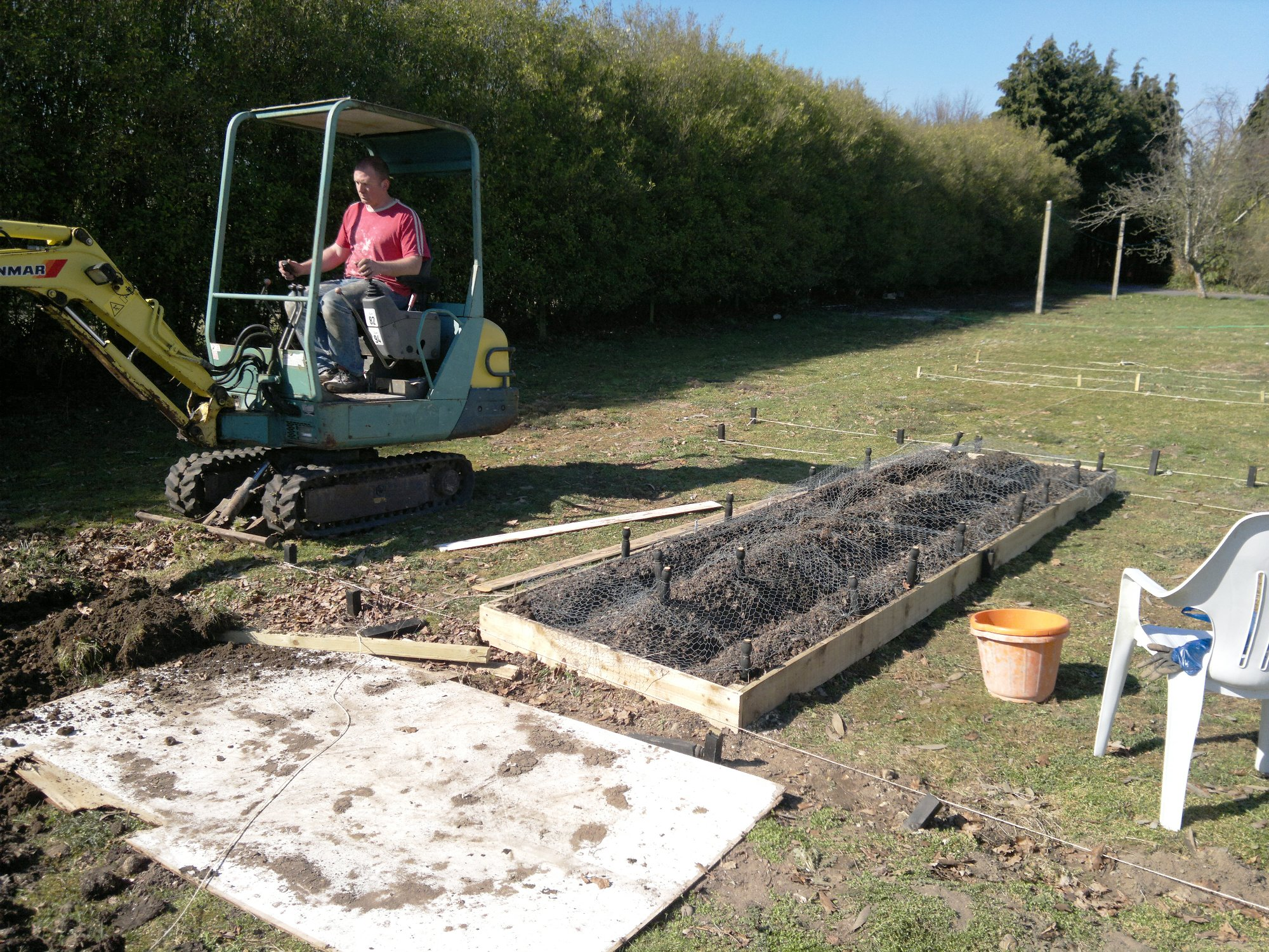 Seth having fun with the big boy's toys; first potato bed in the foreground, protected with wire mesh from the rabbits