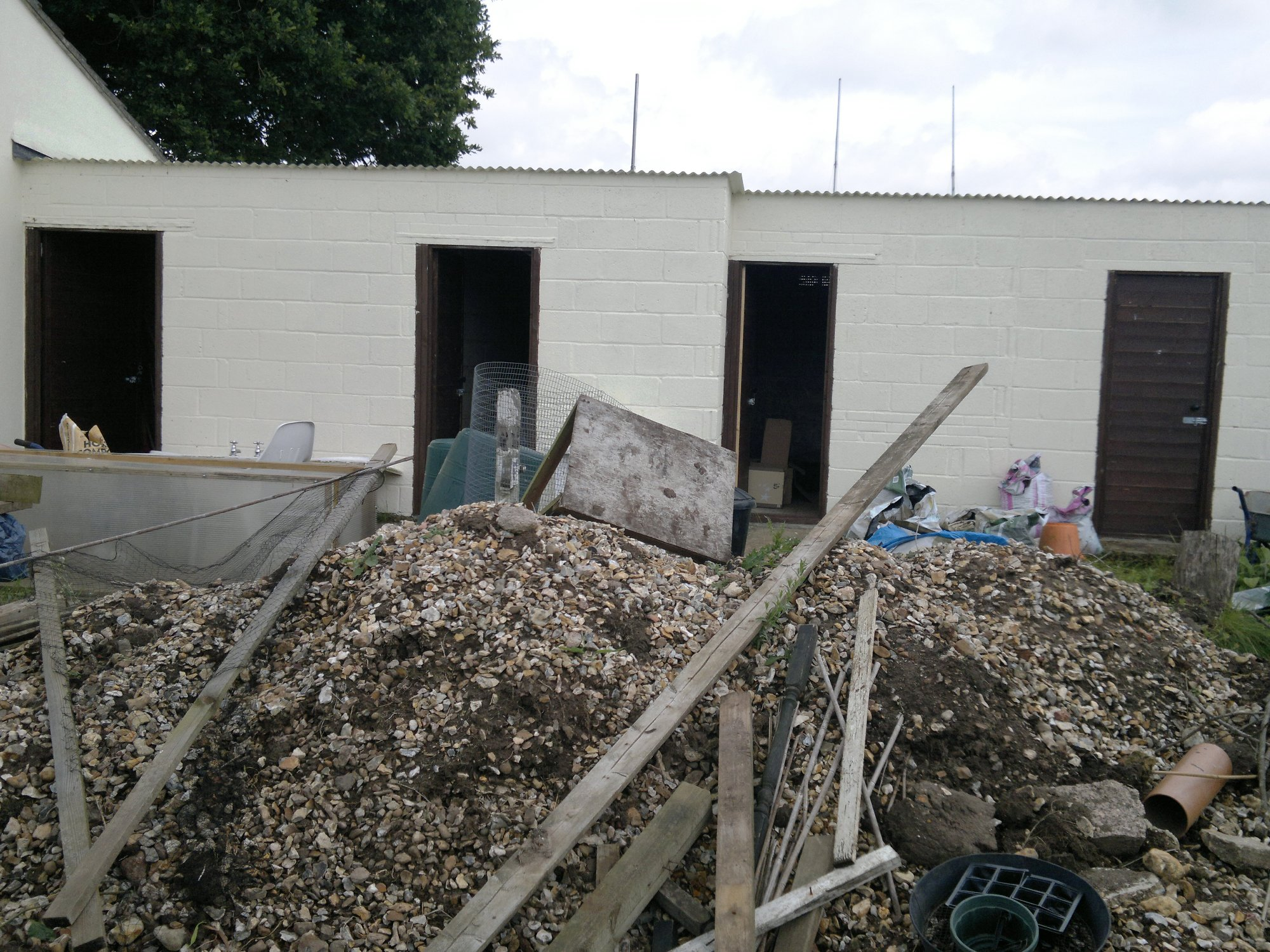 Renovated outbuildings in the background, huge pile of stones sieved from the vegetable beds in the foreground