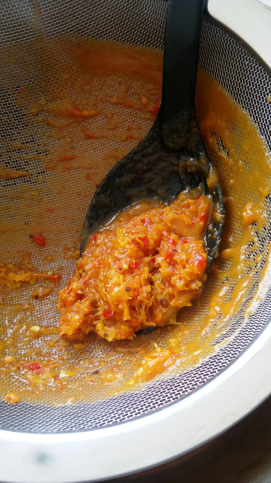 Sieving the sauce to remove pips and fibre