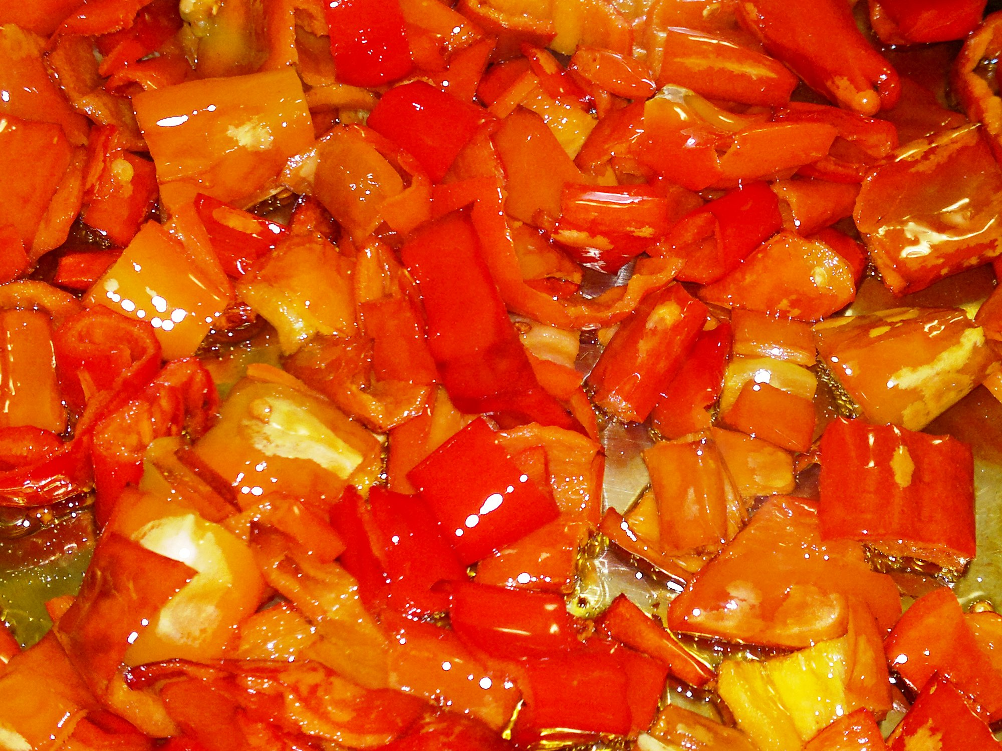 Sliced red peppers cooking gently until soft