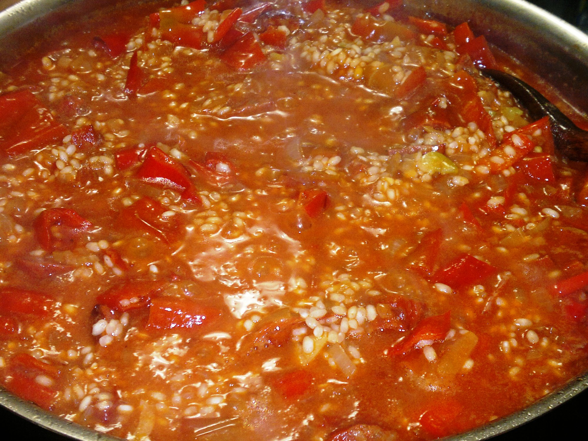 The paella gently bubbling away